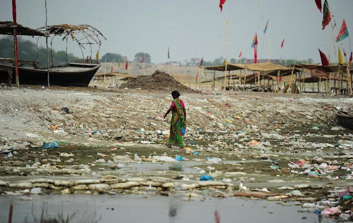 An Indian woman walks amogst plastic bags and garbage strewn on the banks of the River Ganges at Sangam, the confluence of the Ganges, Yamuna and Saraswati rivers in Allahabad on June 3, 2015 (AFP Photo/Sanjay Kanojia)