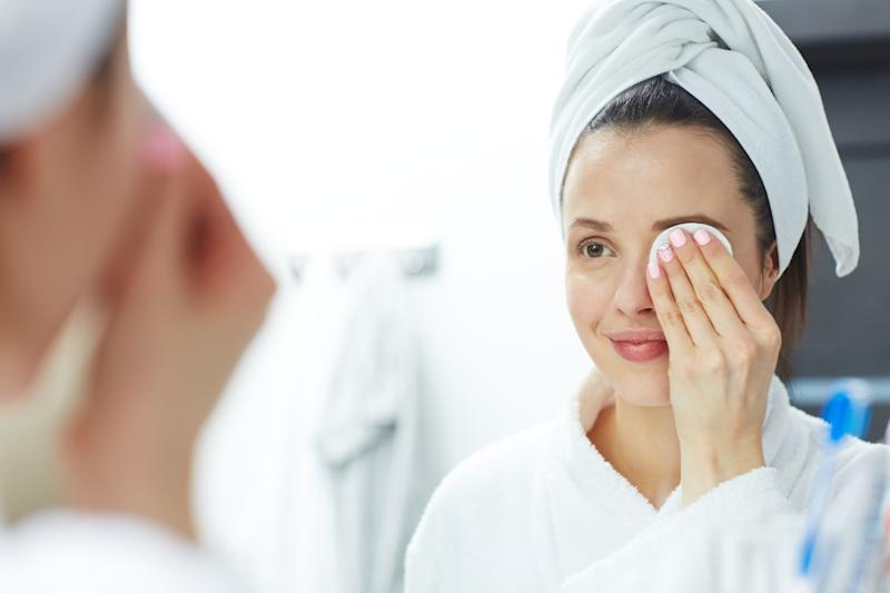 Woman removing makeup with cotton pad