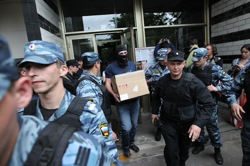 An investigator guarding by Russian police officers carries a box after a police search in Russian opposition leader Alexei Navalny flat in Moscow, Russia, June 11, 2012. Russian investigators searched the apartments of several protest leaders Monday and called them in for questioning Tuesday, making it difficult if not impossible for them to lead a mass demonstration against President Vladimir Putin planned for the June 12 national holiday. (AP Photo/Leonid Lebedev)