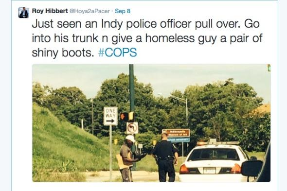 Police officer hands homeless man new boots