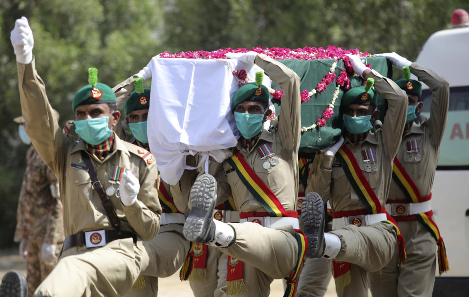 FILE - In this June 1, 2020, file, photo, Pakistani soldiers carry the coffin of their colleague who died in the crash of a state-run Pakistan International Airlines plane May 22, during his funeral in Karachi, Pakistan. The European Union's aviation safety agency said Tuesday, June 30, 2020 that Pakistan's national airline will not be allowed to fly into Europe for at least six months after the country's aviation minister revealed that nearly a third of Pakistani pilots had cheated on their pilot's exams. (AP Photo/Fareed Khan File)