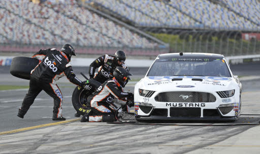 Crew members perform a pit stop on Clint Bowyer's car during qualifying for Saturday's NASCAR All-Star auto race at Charlotte Motor Speedway in Concord, N.C., Friday, May 17, 2019. Bowyer won the pole position for the race. (AP Photo/Chuck Burton)