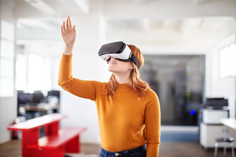 Curious young businesswoman using VR goggles and gesturing. Female executive using virtual reality glasses in office.