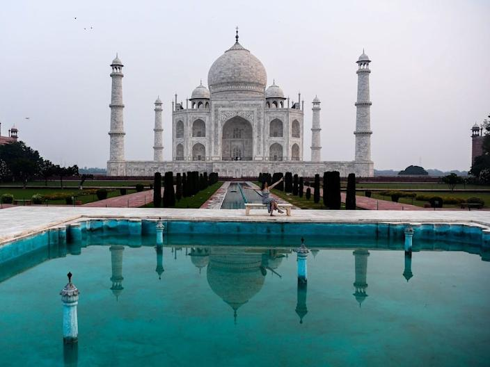 A single tourist takes a picture at the empty Taj Mahal.
