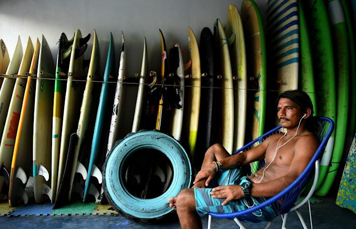 Edwin Omar Zepeda Morales waits for customers at a surf instructing school.