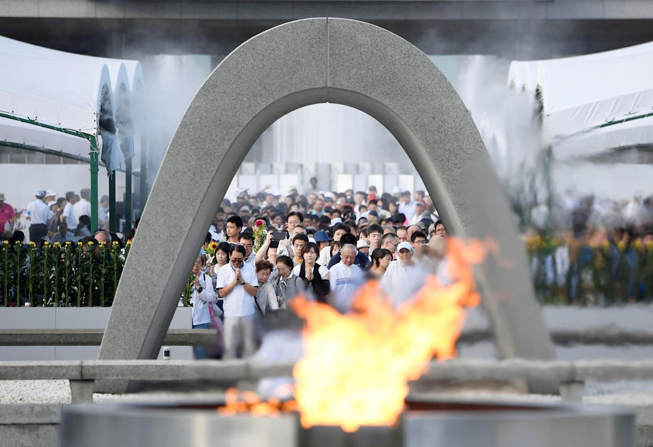 <p>People pray for atomic bomb victims in front of the cenotaph for the victims of the 1945 atomic bombing, at Peace Memorial Park in Hiroshima, western Japan, August 6, 2017, on the 72nd anniversary of the atomic bombing of the city. (Photo: Kyodo via Reuters) </p>