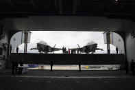 Britain's Queen Elizabeth II , centre, on the flight deck, with a pair of F-35B Lightning II aircraft on either side, during a visit to HMS Queen Elizabeth at HM Naval Base, ahead of the ship's maiden deployment, in Portsmouth, England, Saturday May 22, 2021. HMS Queen Elizabeth will be leading a 28-week deployment to the Far East that Prime Minister Boris Johnson has insisted is not confrontational towards China. (Steve Parsons/Pool Photo via AP)