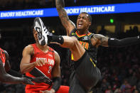 Atlanta Hawks forward John Collins, right, comes down from being fouled while shooting by Portland Trail Blazers center Hassan Whiteside during the first half of an NBA basketball game Saturday, Feb. 29, 2020, in Atlanta. (AP Photo/John Amis)