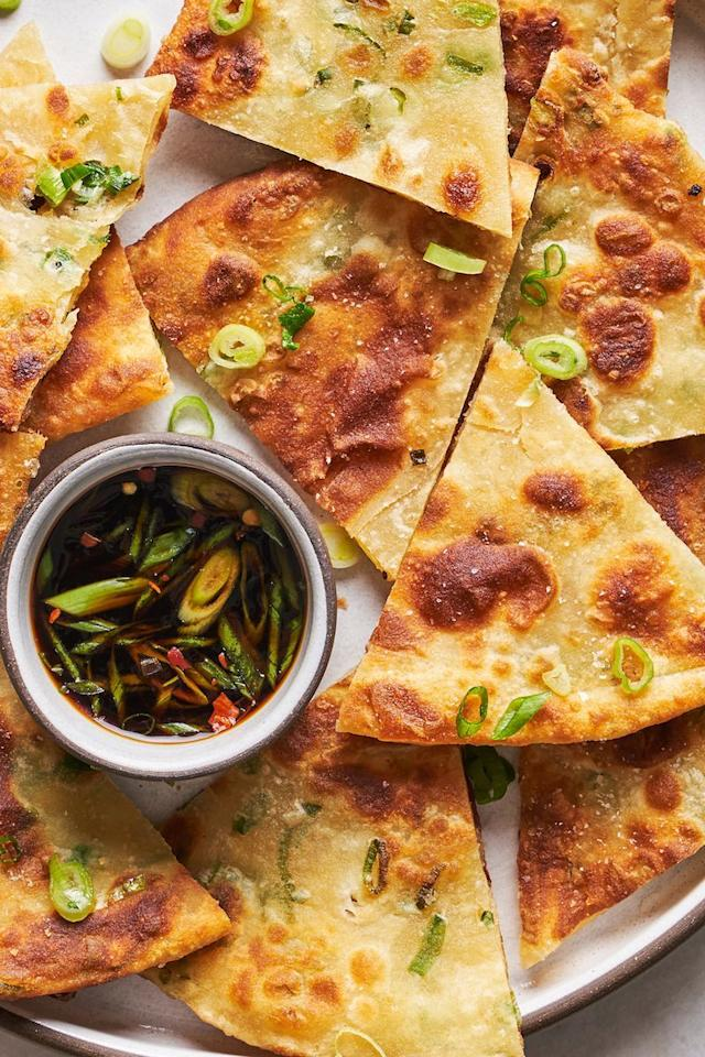 """<p>Spring onion pancakes might be one of our favourite appetisers ever. Crispy, flaky, and with the *slightest* bit of chew, it's easy to polish off a whole plate of them in minutes. </p><p>Get the <a href=""""http://www.delish.com/uk/cooking/recipes/a33009374/scallion-pancakes-recipe/"""" target=""""_blank"""">Spring Onion Pancakes</a> recipe. </p>"""