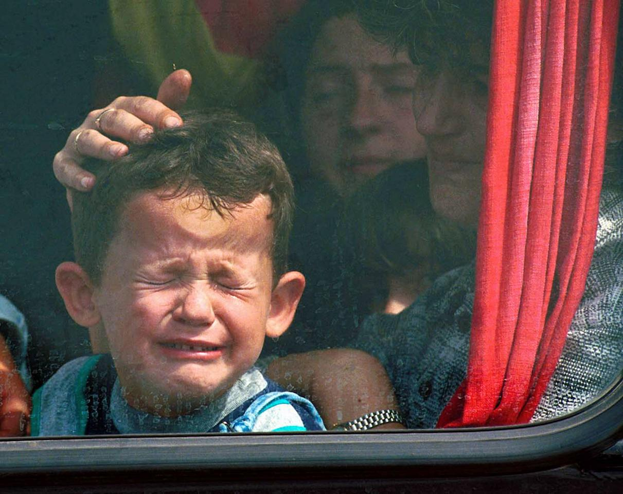 <p>A Serbian boy is comforted as he cries and presses his head against the window of a bus while fleeing the town of Kosovo Polje, outside Pristina, for the town of Nis in Serbia, Sept. 17, 1999. (Photo: Jacqueline Larma/AP) </p>