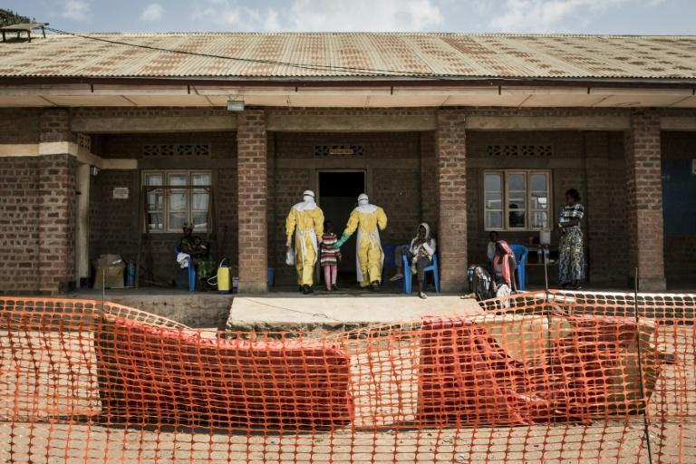 Medical workers lead a young girl with suspected Ebola into the unconfirmed Ebola patients ward run by The Alliance for International Medical Action (ALIMA) in Beni, northeastern DRC