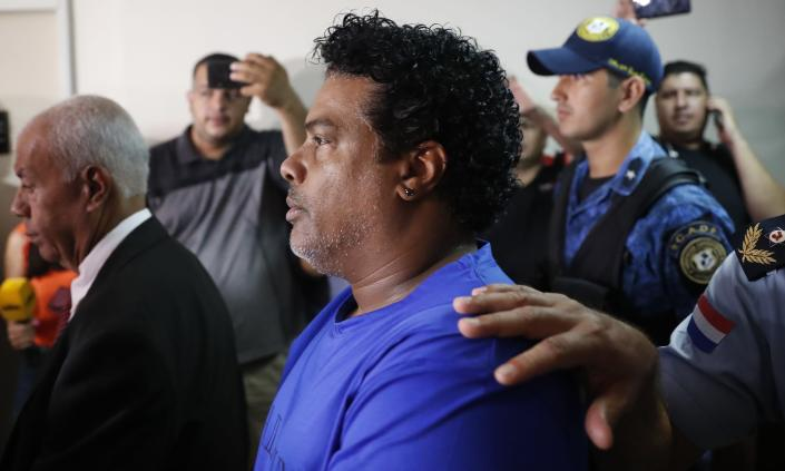 Ronaldinho's brother Roberto de Assis Moreira walks escorted by Police officers to declare to judge Clara Ruiz Diaz at Justice Palace in Asuncion, Paraguay, Saturday, March 7, 2020. Ronaldinho and his brother Roberto were alleged to enter to the country with a false Paraguayan passport.(AP Photo/Jorge Saenz)