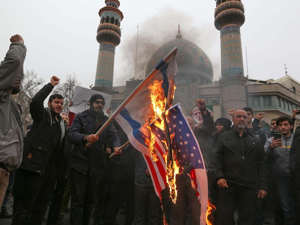 Iranians burn US and Israeli flags during an anti-US protest over the killings during a US air strike of Iranian military commander Qasem Soleimani and Iraqi paramilitary chief Abu Mahdi al-Muhandis, in the capital Tehran on January 4 (AFP via Getty Images)