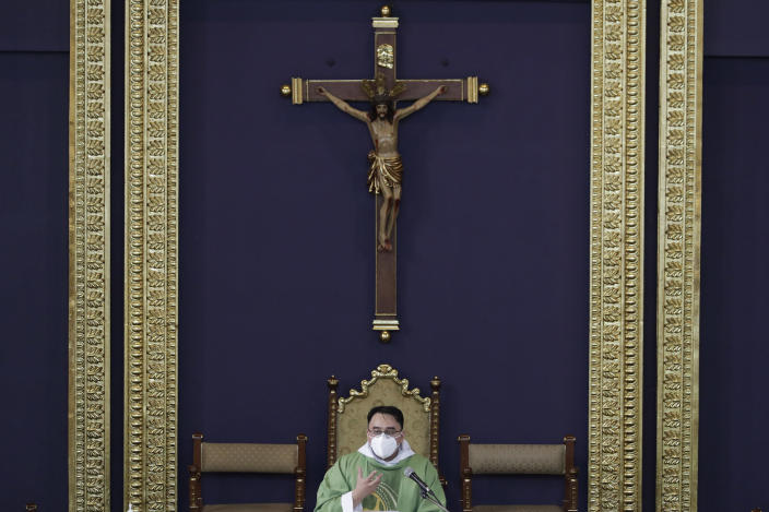 Catholic priest Fr. Ian Espartero gestures as he officiates mass with a few parishioners as a measure to prevent the spread of COVID19 at the Our Lady of Consolation Parish on Sunday, Aug. 2, 2020, in Quezon city, Philippines. Coronavirus infections in the Philippines continues to surge Sunday as medical groups declared the country was waging a losing battle against the contagion and asked the president to reimpose a lockdown in the capital. (AP Photo/Aaron Favila)