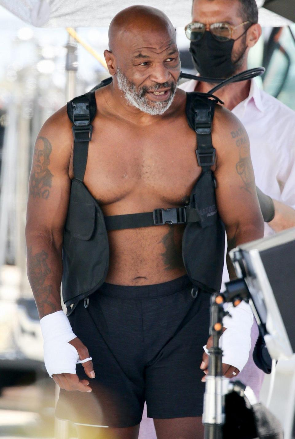<p>Mike Tyson shows off his muscles on Wednesday during a photo shoot on the beach in Los Angeles. </p>