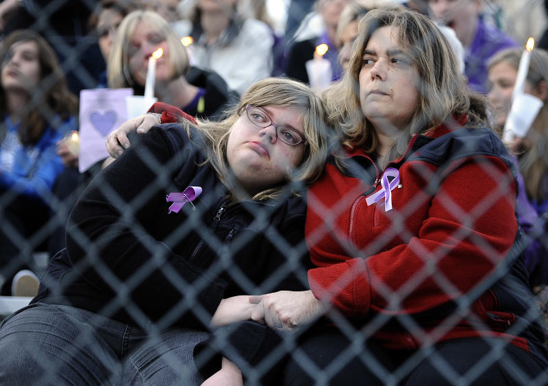A woman and child hold hands as they sit on the bleachers during a vigil for Maren Sanchez at Jonathan Law High School, Monday, April 28, 2014, in Milford, Conn. Sanchez was fatally stabbed inside the school on Friday hours before her junior prom. (AP Photo/Jessica Hill)