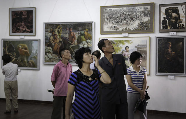 FILE - In this July 26, 2015, file photo, North Koreans look at paintings on display in Pyongyang, North Korea. South Korea says on Wednesday, Jan. 16, 2019, it has stopped businessmen from bringing in North Korean paintings in a potential violation of UN sanctions. (AP Photo/Wong Maye-E, File)