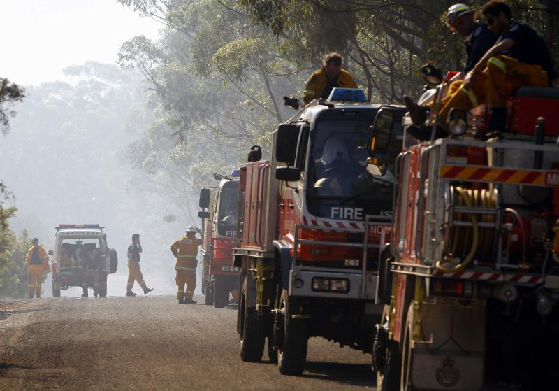 Rural Fire Service firefighters take a break after trying to extinguish a fire approaching homes near the Blue Mountains suburb of Faulconbridge