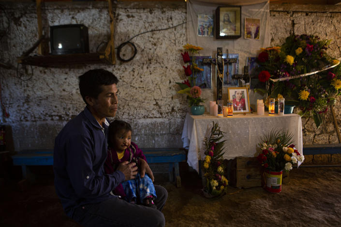 Ricardo Garcia and daughter Angela sit next to an altar adorned with photographs of his older daughter Santa Garcia, in his home in Comitancillo, Guatemala, Wednesday, Jan. 27, 2021. He believes his daughter Santa is one of the charred corpses found in a northern Mexico border state on Saturday. The country's Foreign Ministry said it was collecting DNA samples from a dozen relatives to see if there was a match with any of the bodies. (AP Photo/Oliver de Ros)