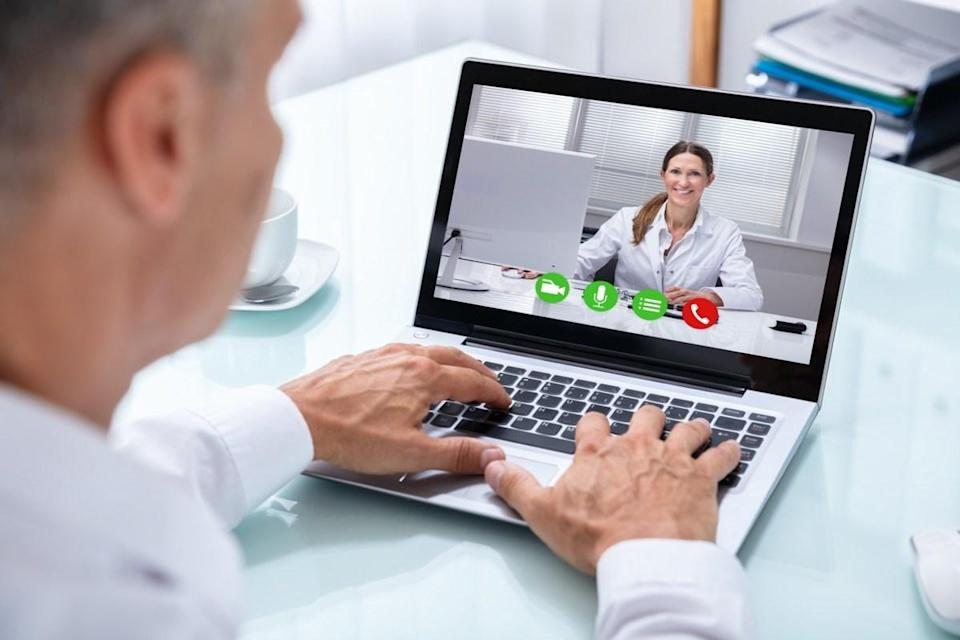 Videoconferencing With Happy Female Doctor On Laptop