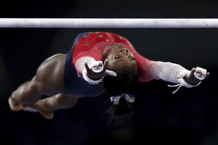 File-This Oct. 8, 2019, file photo shows Simone Biles of the U.S. warming up on the uneven bars during women's team final at the Gymnastics World Championships in Stuttgart, Germany. Biles is the 2019 AP Female Athlete of the Year. She is the first gymnast to win the award twice and the first to win it in a non-Olympic year. (AP Photo/Matthias Schrader, File)