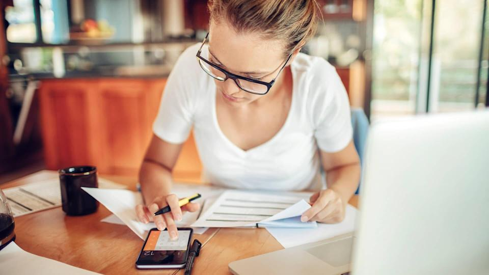 Close up of a young woman sitting in kitchen and  going through her financials.