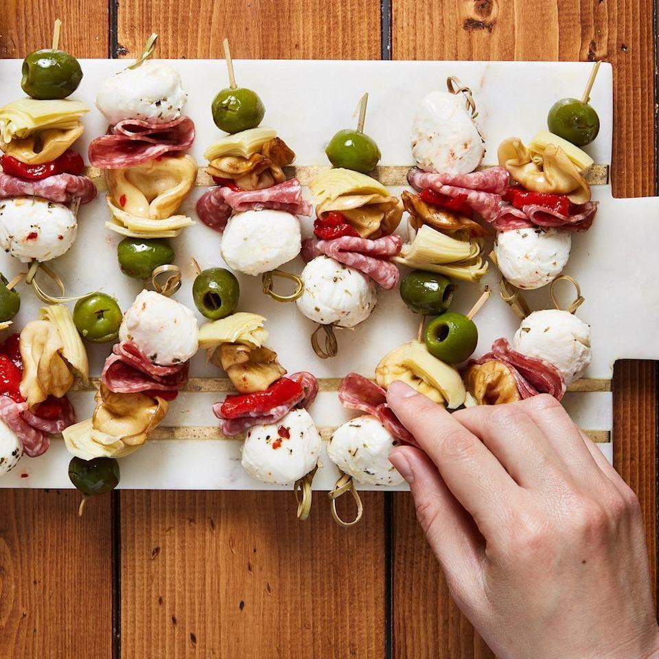 """<p>Fresh tortellini makes this the hearty appetiser of our dreams. If you're not a fan of olives, pepperoncini peppers would be a delicious substitute! </p><p>Get the <a href=""""https://www.delish.com/uk/cooking/recipes/a35262428/antipasto-bites-recipe/"""" rel=""""nofollow noopener"""" target=""""_blank"""" data-ylk=""""slk:Antipasto Bites"""" class=""""link rapid-noclick-resp"""">Antipasto Bites</a> recipe.</p>"""