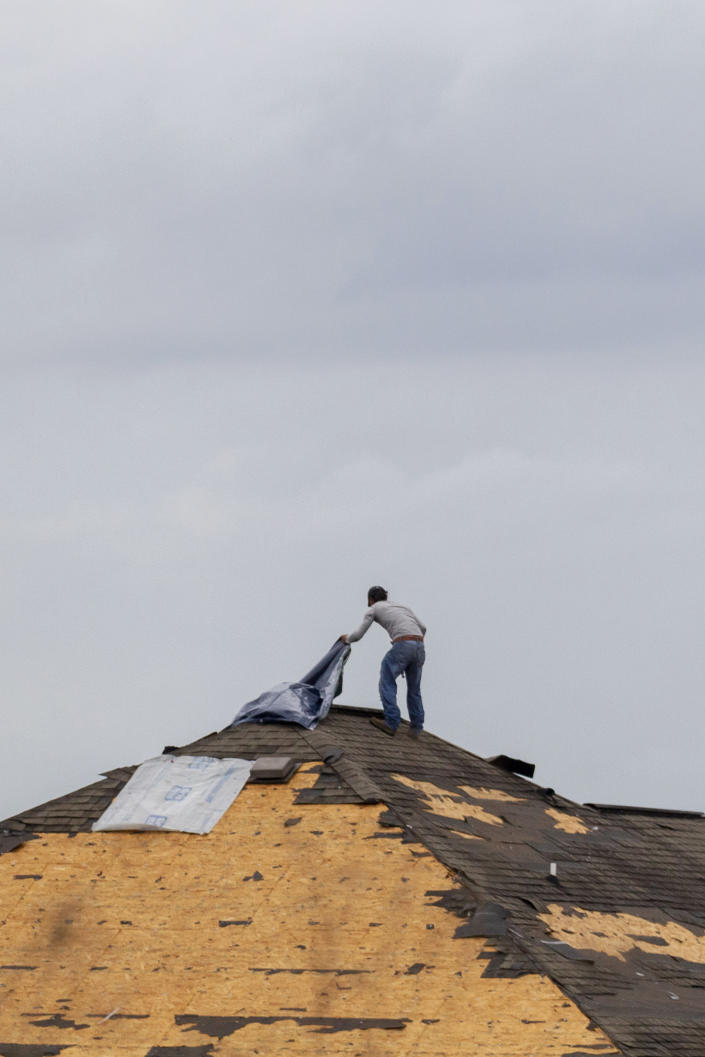 A worker checks the damage to the roof of a house being built along State Road 69 as severe weather hit, Wednesday, March 17, 2021, in Moundville, Ala. Possible tornadoes knocked down trees, toppled power lines and damaged homes in rural Chilton County and the Alabama communities of Burnsville and Moundville, where power was out and trees blocked a main highway. (AP Photo/Vasha Hunt)