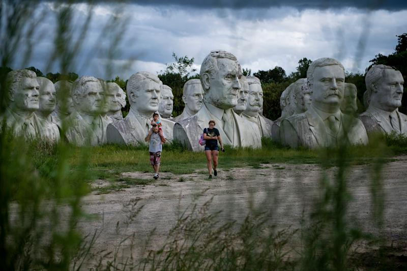 People walk past decaying busts of former US Presidents near the mulching facility where they now reside on August 25, 2019, in Williamsburg, Virginia. (Photo: Brendan Smialowski/AFP/Getty Images)