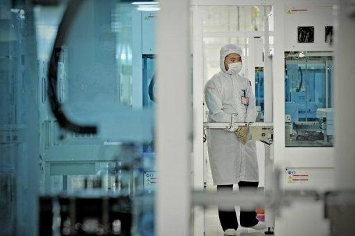 File photo of a worker making solar cells at a Trina Solar plant in Changzhou, China. Four leading firms in China warned Thursday that a possible EU anti-dumping investigation could trigger a trade war and urged Beijing to step in to protect their interests
