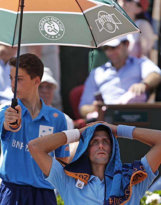 Serbia's Novak Djokovic takes cover from the sun during the semifinal match of the French Open tennis tournament against Latvia's Ernests Gulbis at the Roland Garros stadium, in Paris, France, Friday, June 6, 2014. Djokovic won in four sets 6-3, 6-3, 3-6, 6-3. (AP Photo/Darko Vojinovic)