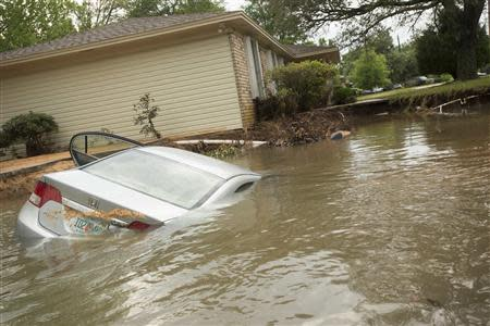 A submerged car sits in the driveway in the Cordova Park neighborhood in Pensacola, Florida