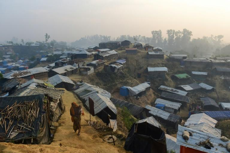Photo taken last November shows a Rohingya refugee woman walking with a child in her lap in Balukhali refugee camp in Bangladesh