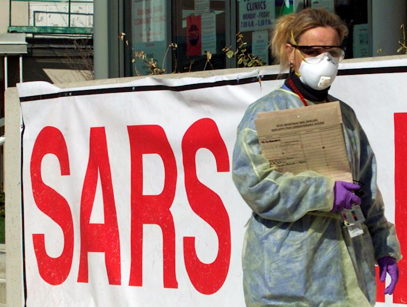 FILE PHOTO: A nurse wearing protective gear walks outside a Severe Acute Respiratory Syndrome Clinic (SARS) in suburban Toronto, April 24, 2003. REUTERS/Mike Cassese/File Photo