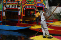 A gondolier poles one of the colorfully painted wooden boats known as trajineras at the Nuevo Nativitas dock, as it opens once again to tourists and revelers amidst the ongoing new coronavirus pandemic, the Xochimilco borough of Mexico City, Friday, Aug. 21, 2020. Though traffic was light on the first day back after being closed for several months, gondoliers, handicraft sellers, and food and drink vendors said they were happy to be back at work and to have the chance to earn some money. (AP Photo/Rebecca Blackwell)