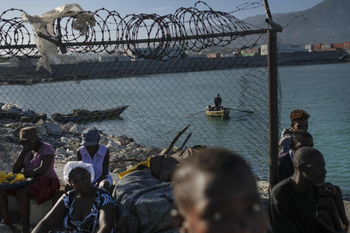 A fisherman rows his boat near the shore where vendors sell food and workers wait to unload merchandise from boats in the La Saline neighborhood of Port-au-Prince, Haiti, Monday, July 19, 2021. The country of more than 11 million people is still reeling from the July 7 killing of President Jovenel Moise. (AP Photo/Matias Delacroix)