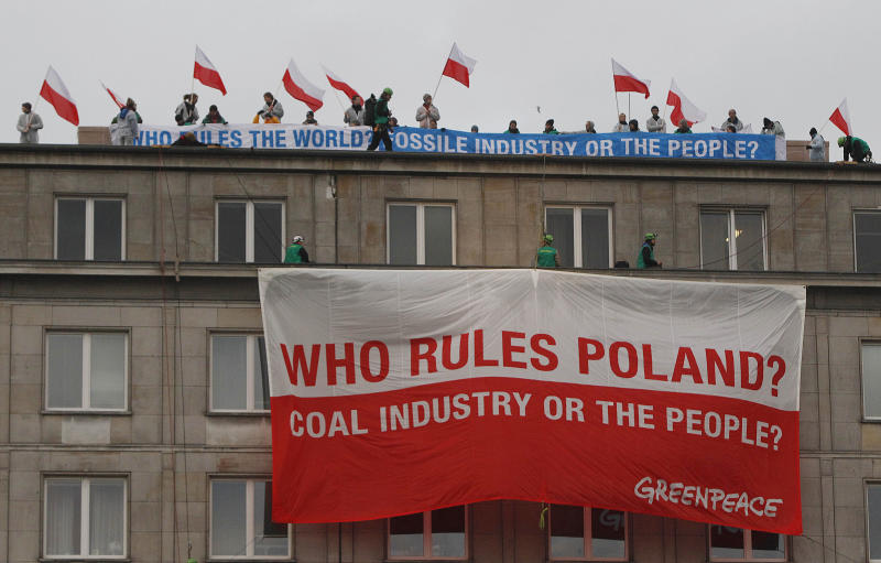 Climate activists with protest banners wave polish flags on the rooftop of the Economy Ministry in Warsaw, Poland Monday, Nov. 18, 2013. They went up the rooftop to protest a coal conference opening to coincide with U.N. talks on preventing global warming, that is also the result of greenhouse gases coming from burning coal. (AP Photo/Czarek Sokolowski)