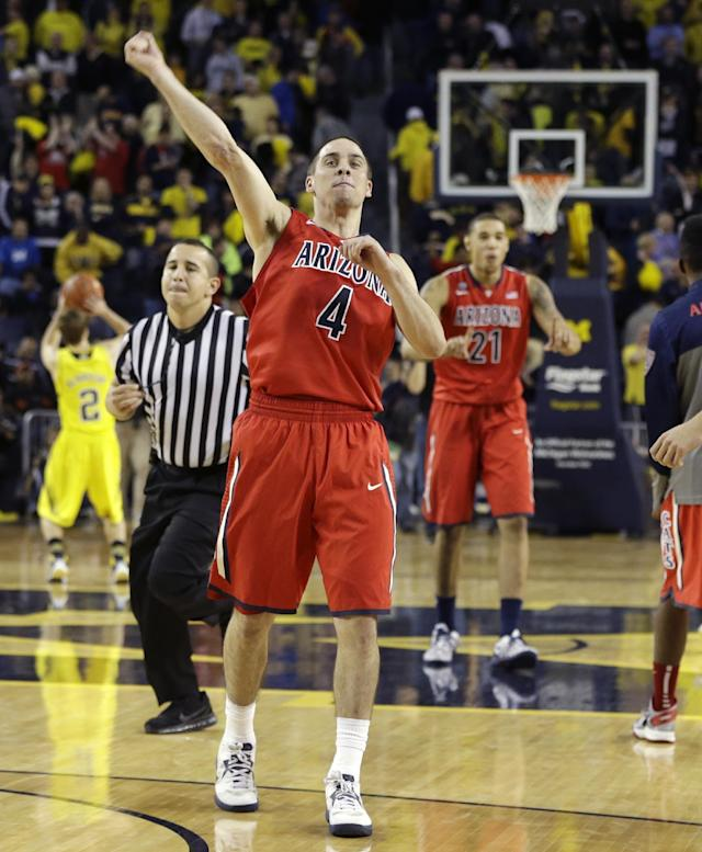 Arizona guard T.J. McConnell (4) celebrates after the Wildcats defeated Michigan 72-70 in an NCAA college basketball game in Ann Arbor, Mich., Saturday, Dec. 14, 2013. (AP Photo/Carlos Osorio)
