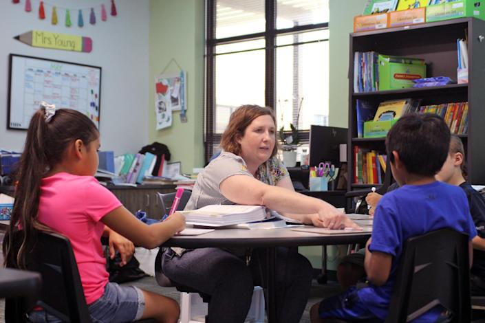 Rebecca Young works on phonics with several rising first grade students during a summer school program at River Bend Elementary in College Station, Texas. (Jackie Mader / The Hechinger Report)