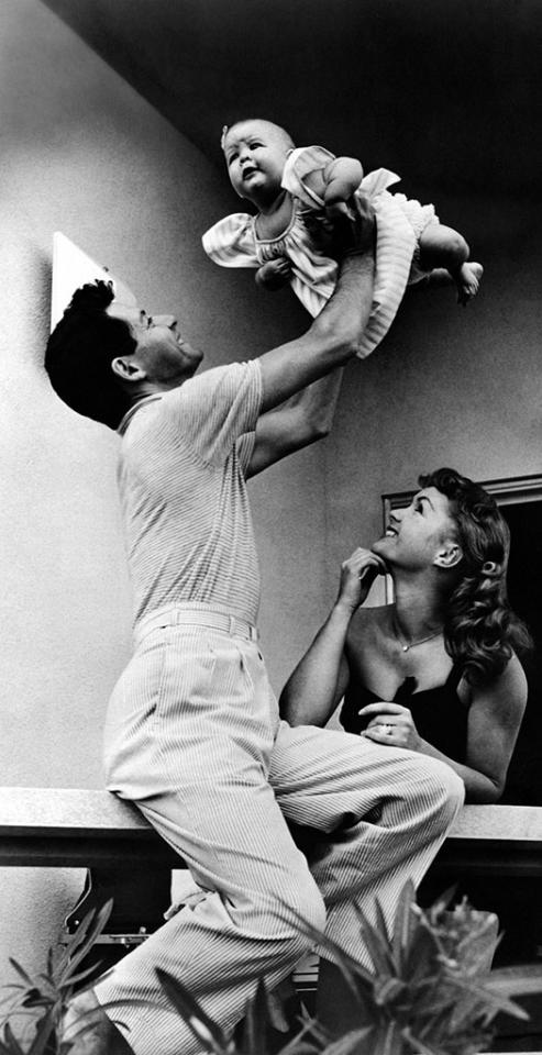 <p>Singer Eddie Fisher playfully tosses his daughter in the air as his wife, Debbie Reynolds, looks on. (Photo: Mondadori Portfolio via Getty Images) </p>