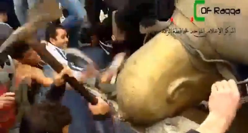 FILE - In this Monday, March 4, 2013 file image taken from video obtained from Ugarit News, which has been authenticated based on its contents and other AP reporting, shows a statue of former Syrian President Hafez Assad is pulled down in a central square in Raqqa, Syria. A quiet power struggle in taking place in the eastern city between Islamic extremist rebels, who control the city after capturing it four months ago from the regime, and moderates trying to curtail their influence, making it a test case for the opposition.(AP Photo/Ugarit News via AP video, File)