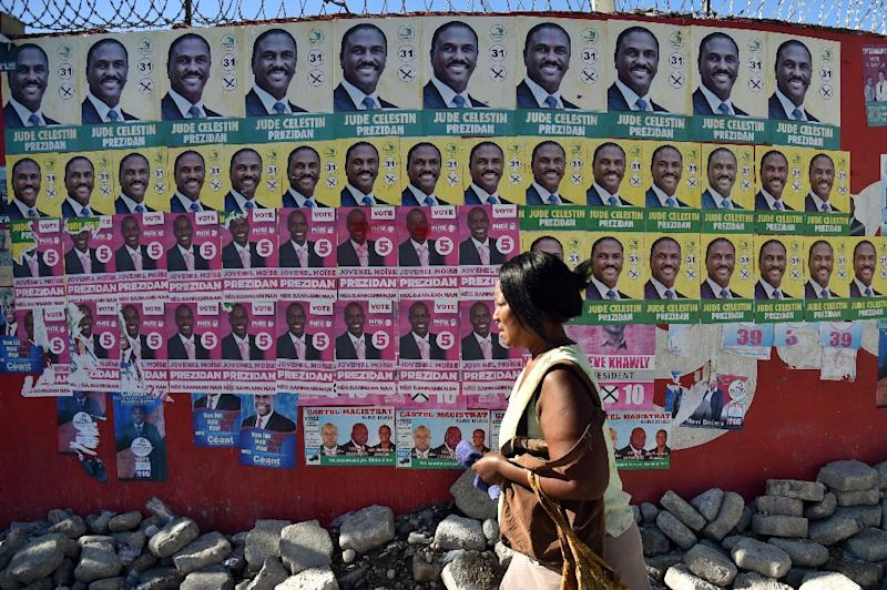 A woman walks by election posters of presidential candidates Jovenel Moise of the PHTK political party and Jude Celestin of the LAPEH political party, in Port-au-Prince on November 6, 2015 (AFP Photo/Hector Retamal)