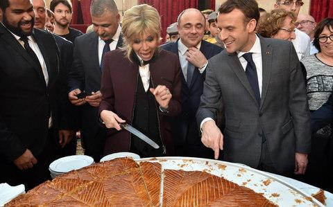 French president Emmanuel Macron (R) and his wife Brigitte (C) cut slices of a traditional epiphany cake during a ceremony at the Elysee palace on January 12 - Credit: Christophe Archambault/AFP