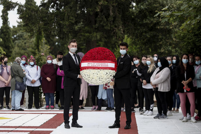 """Two youths hold a wreath which is to be laid by Turkish Foreign Minister Mevlut Cavusoglu at a muslim cemetery at Komotini town, in northeastern Greece, Sunday, May 30, 2021. Greece's prime minister said Friday his country is seeking improved ties with neighbor and longtime foe Turkey, but that the onus is on Turkey to refrain from what he called """"provocations, illegal actions and aggressive rhetoric."""" (AP Photo/Giannis Papanikos)"""