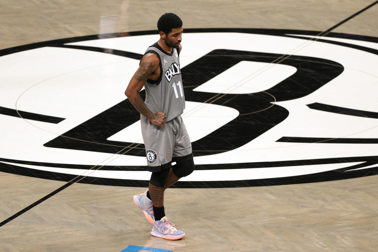 Kyrie Irving with his hands on his hips and looking down at the court near midcourt and the Brooklyn Nets logo.