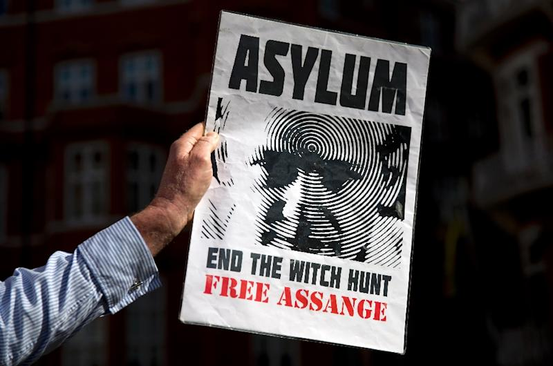 A supporter of Julian Assange holds a banner he marks three years since the Wikileaks founder claimed asylum inside the Ecuadorian embassy in London, on June 19, 2015 (AFP Photo/Justin Tallis)