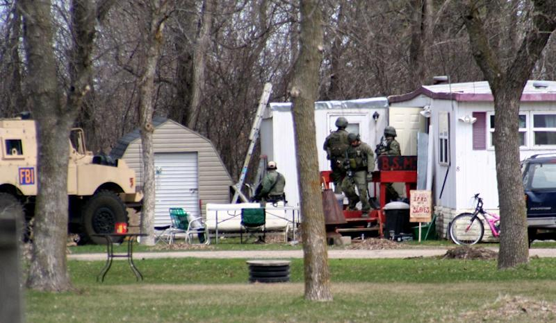 This May 3, 2013, photo provided by Jeremy Jones shows FBI agents during a raid on a mobile home in Montevideo, Minn. Authorities said Monday, May 6, that Rogers was arrested Friday and that the agency believes is disrupted a potential terror attack after a search of the home turned up Molotov cocktails, suspected pipe bombs and firearms. (AP Photo/Montevideo American-News, Jeremy Jones) MANDATORY CREDIT