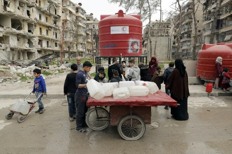 Syrians stand in line at a water tank in the once rebel-held Shaar neighbourhood of the Syrian city of Aleppo on March 9, 2017