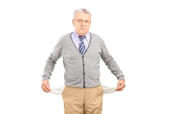 A senior man with his pockets turned inside out, showing that he has no money.