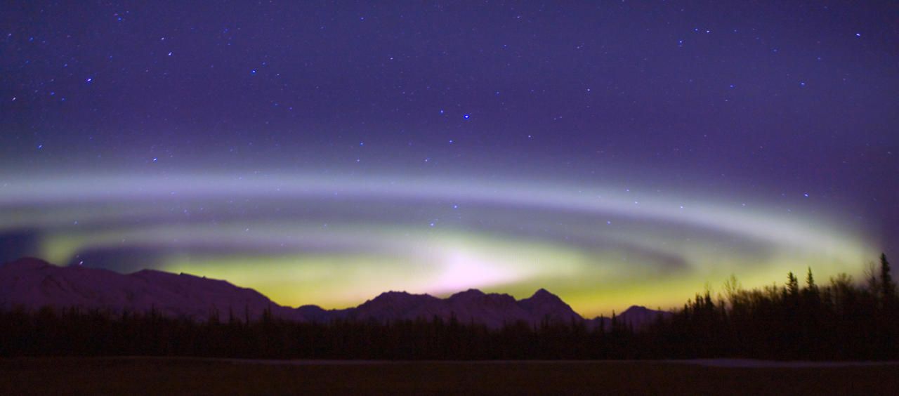 An Aurora Borealis spins above the Talkeetna Range and a hay field on Farm Loop Road near Palmer, Alaska, on Friday, Feb. 29, 2008. The center of the circular corona, usually near Earth's north pole sometimes fluctuates further south and can be seen from a lower latitude as in this instance. (AP Photo/Bob Martinson)